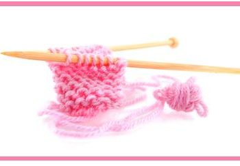 Knitting with pink wool and wooden needles